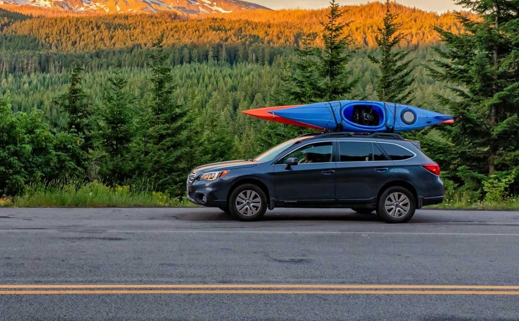 SUV with kayaks in front of mountain at sunset