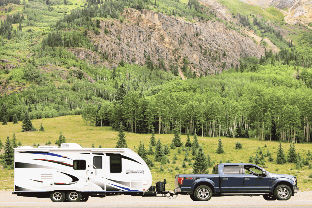 A Ford F-150 truck and Lance travel trailer are pulled to the roadside in the San Juan Mountains