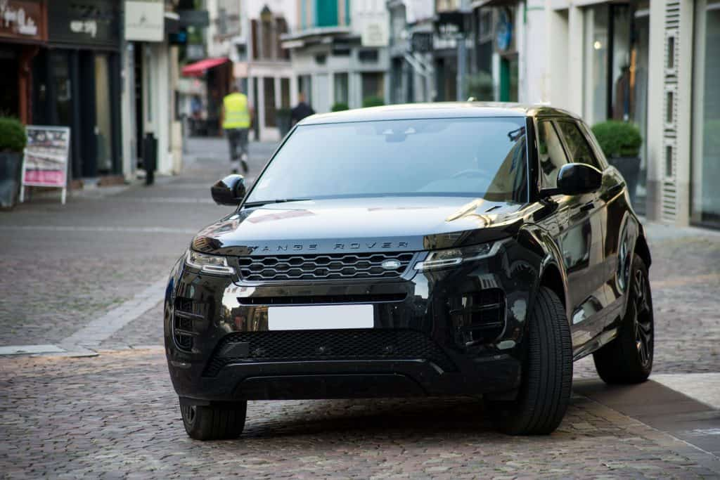 A Range Rover Velar moving on the streets on a busy road, What SUVs Have Blind Spot Detection? [2021 Midsize And Full-Size]