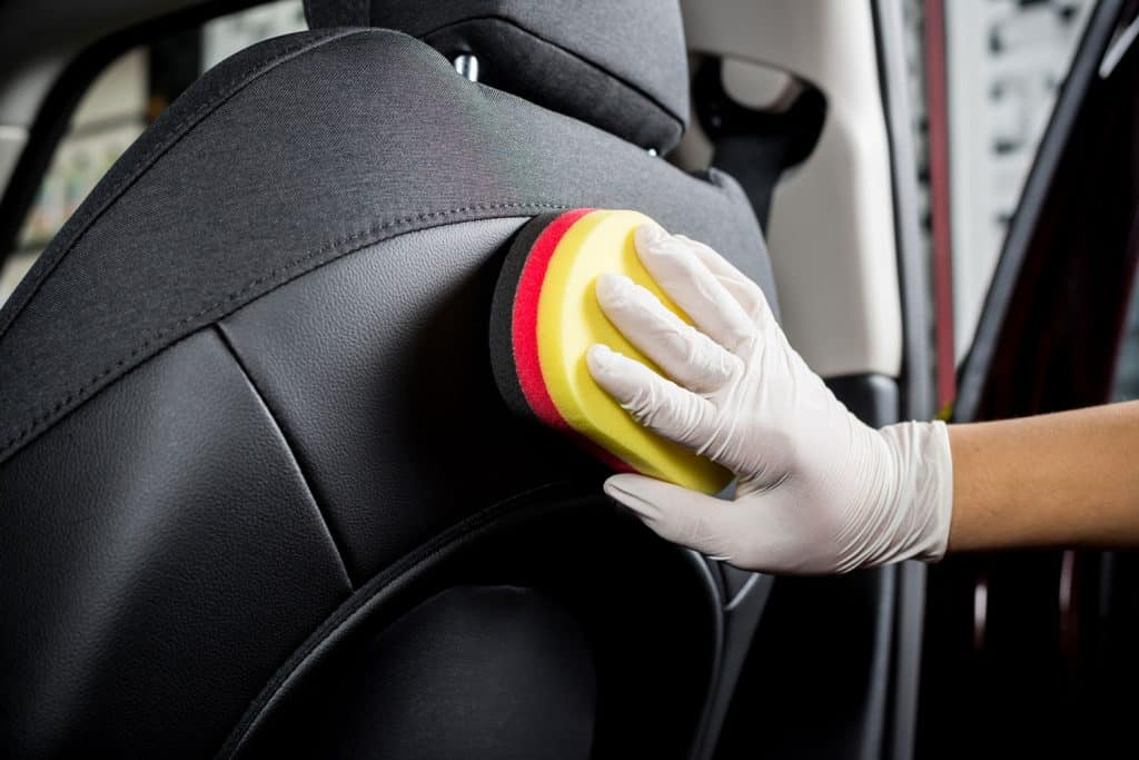 A car auto detailer scrubbing the leather seats in the interior of a car