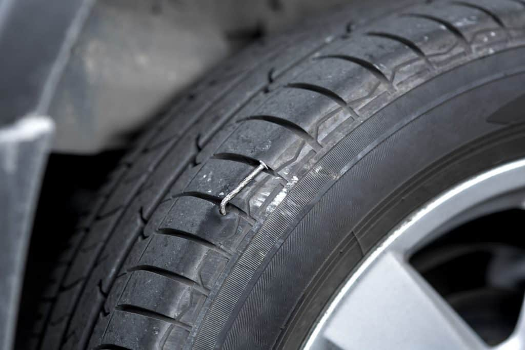 A huge nail lodge into the car tire, Can You Fix A Tire With A Nail In It? [And How To]