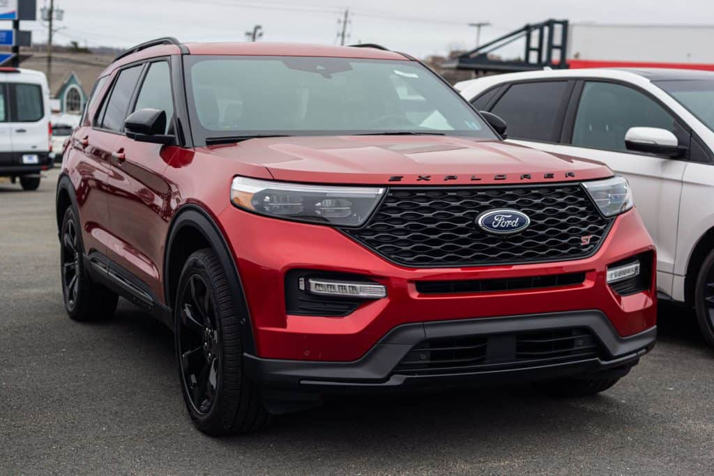 A luxurious red colored Ford Explorer parked outside a parking lot