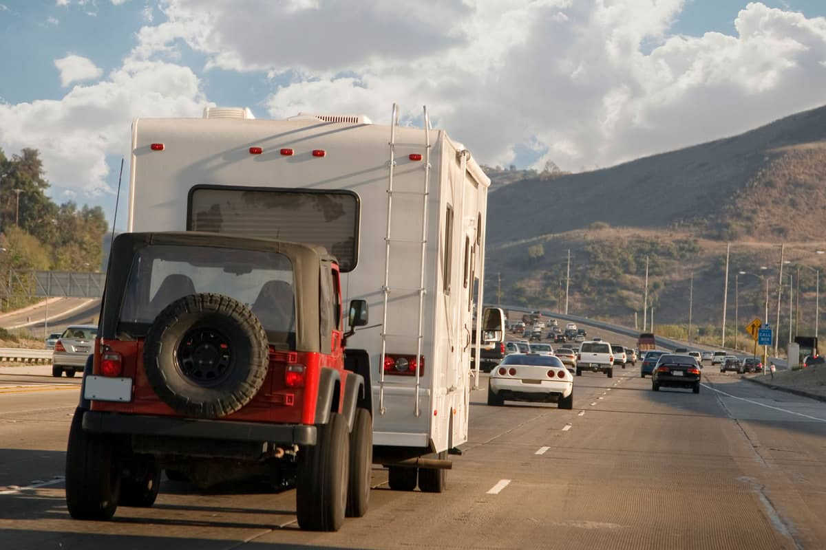 An rv towing a red jeep