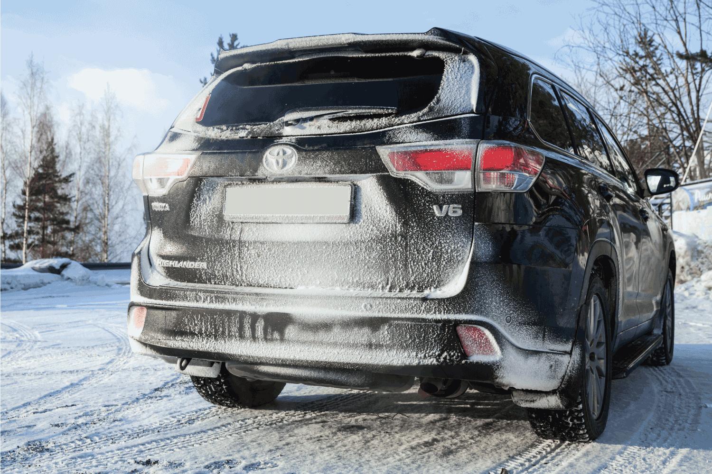 Black Toyota Highlander car stands on a roadside in winter season, rear view