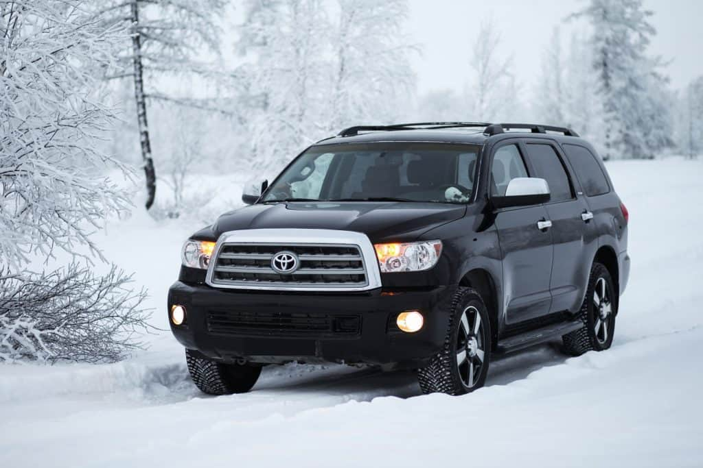 Black luxury SUV car Toyota Sequoia in the snow covered winter forest