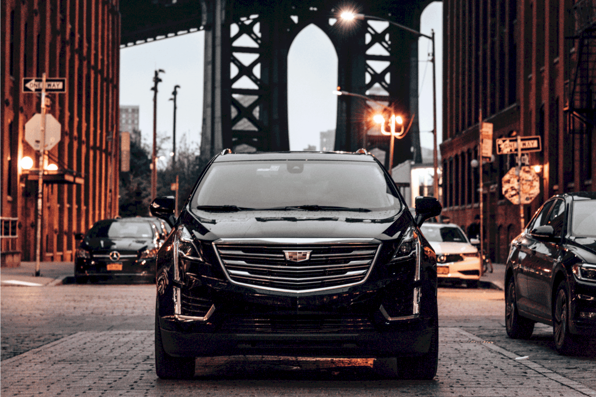 Cadillac XT5 is parked along the street of Dumbo district in Brooklyn with the Manhattan Bridge in the background