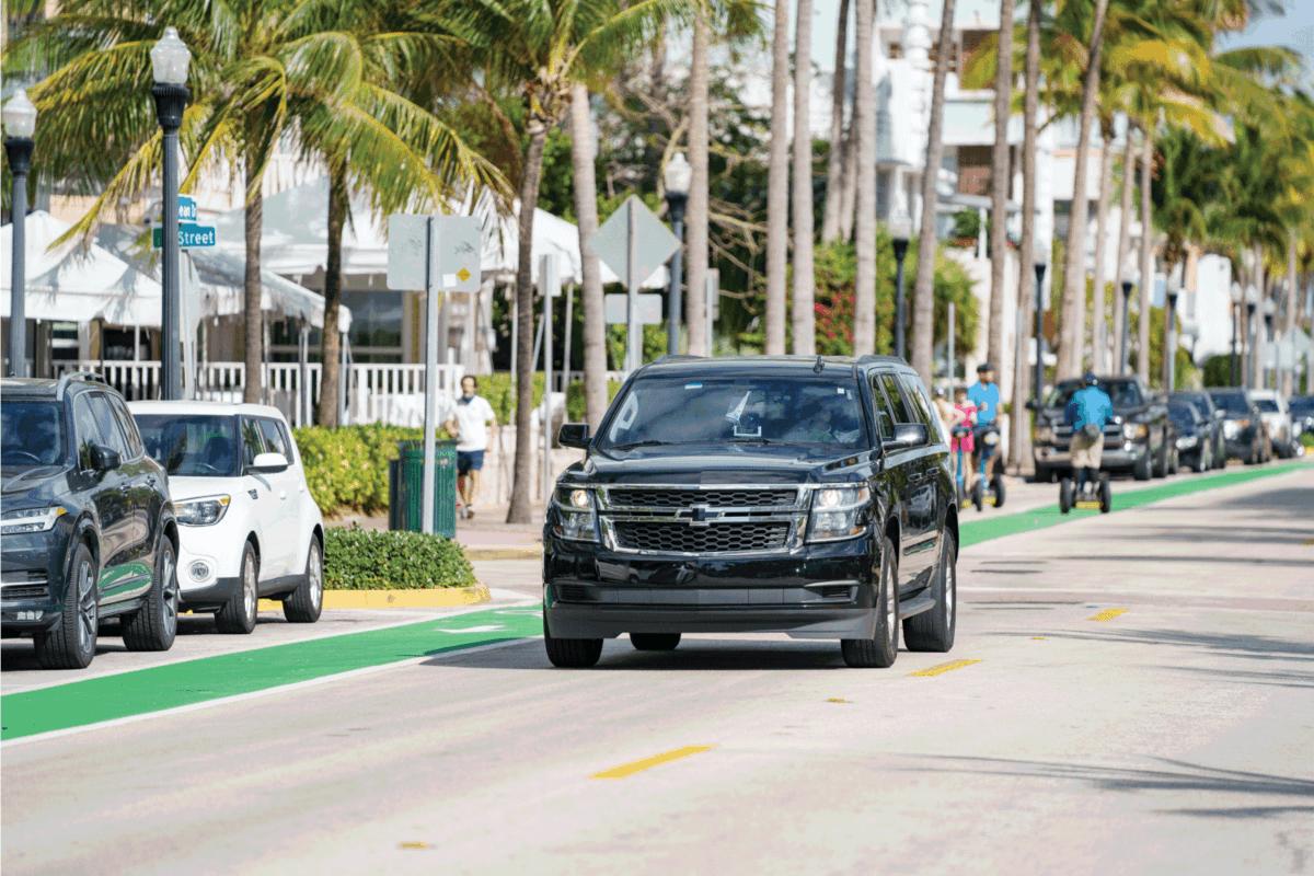 Chevy Suburban lux suv rideshare vehicle cruising Miami Beach Ocean Drive