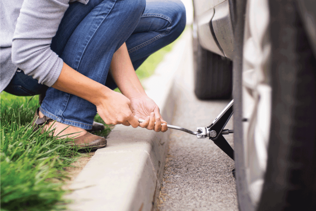 Closeup of unrecognizable woman changing flat tire on her car. She's kneeling on the roadside next to rear left wheel and lifting car jack. What SUVs Have Full-Size Spare Tires
