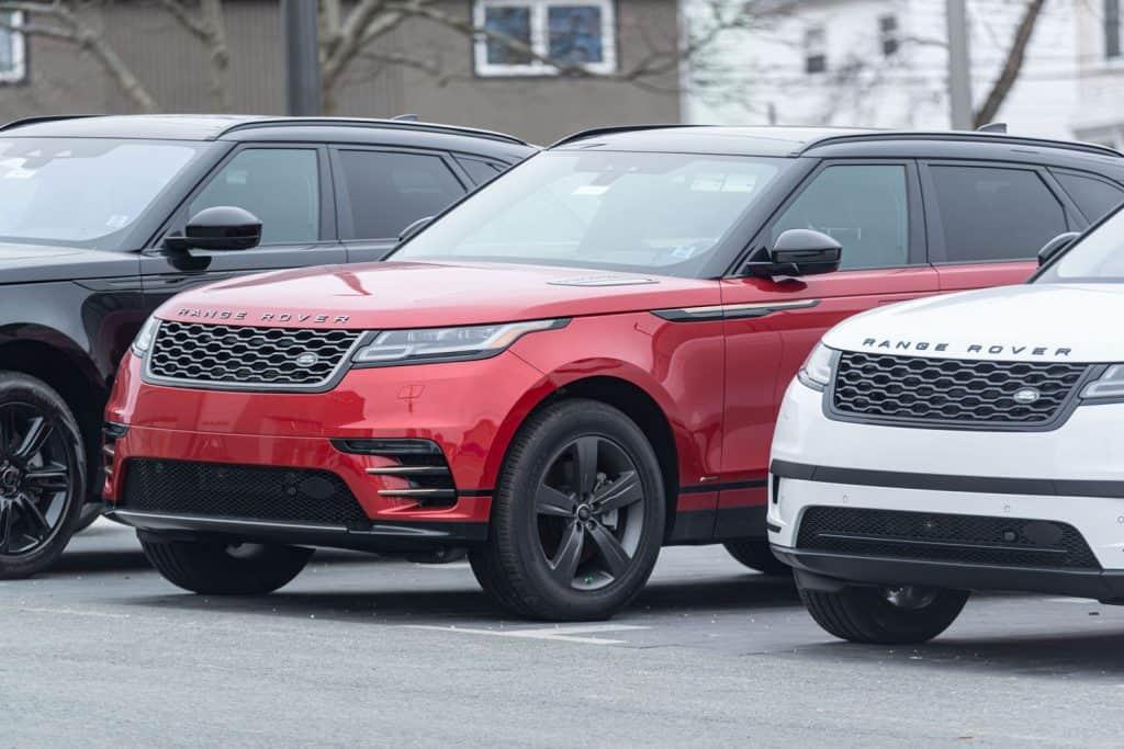 Different colored Range Rover Velar SUVs parked outside a dealership