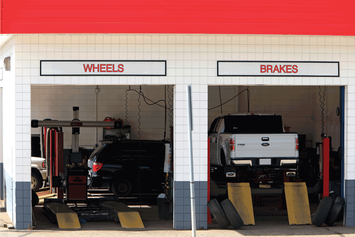 Exterior/Interior of two Service Bays for cars and trucks. Hydraulic hoists and ramps. One white truck on lift.