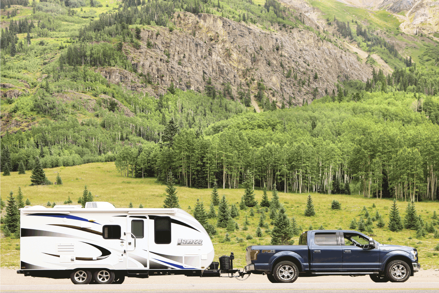 Ford F-150 truck and Lance travel trailer are pulled to the roadside in the San Juan Mountains.