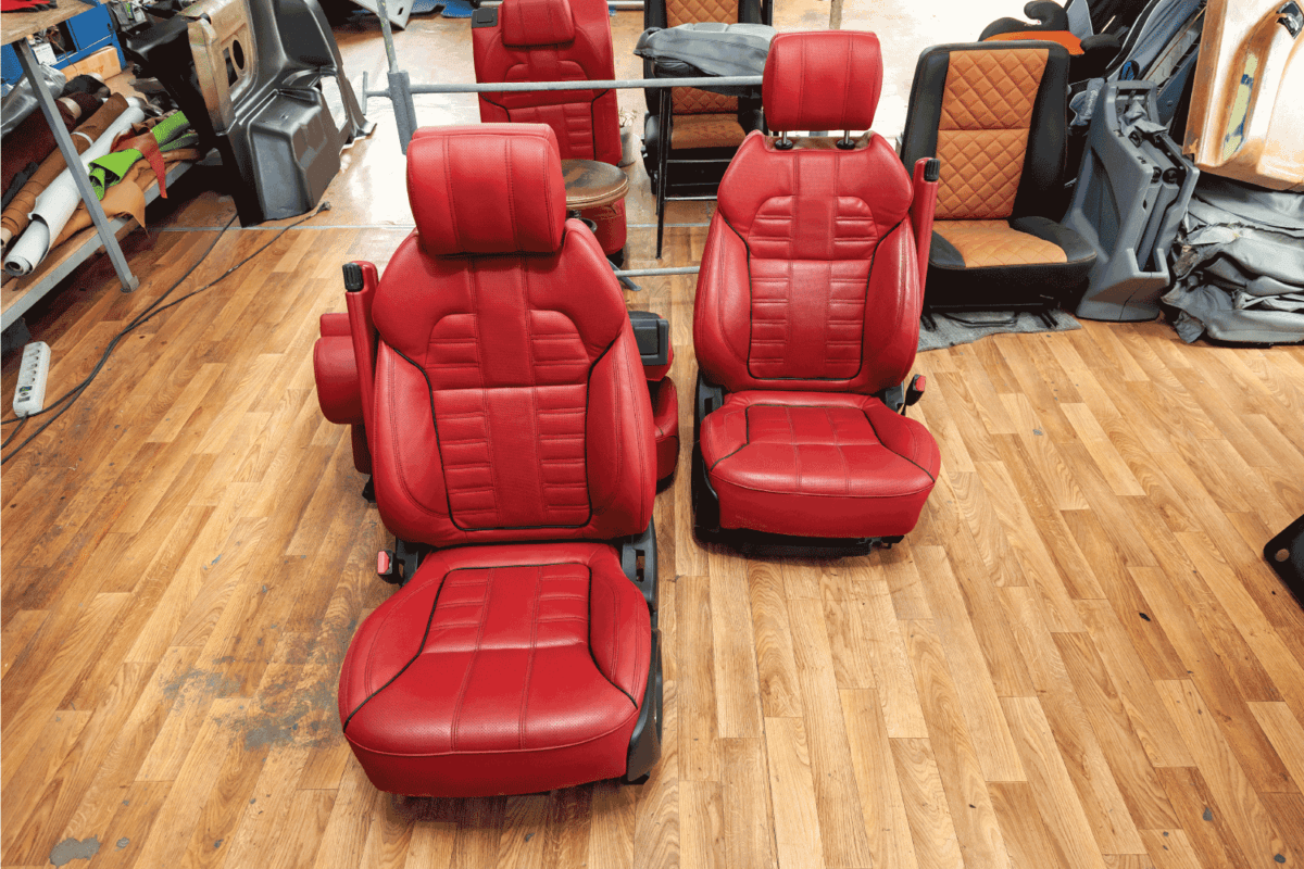 Four sport seats with red leather trim, located on the floor