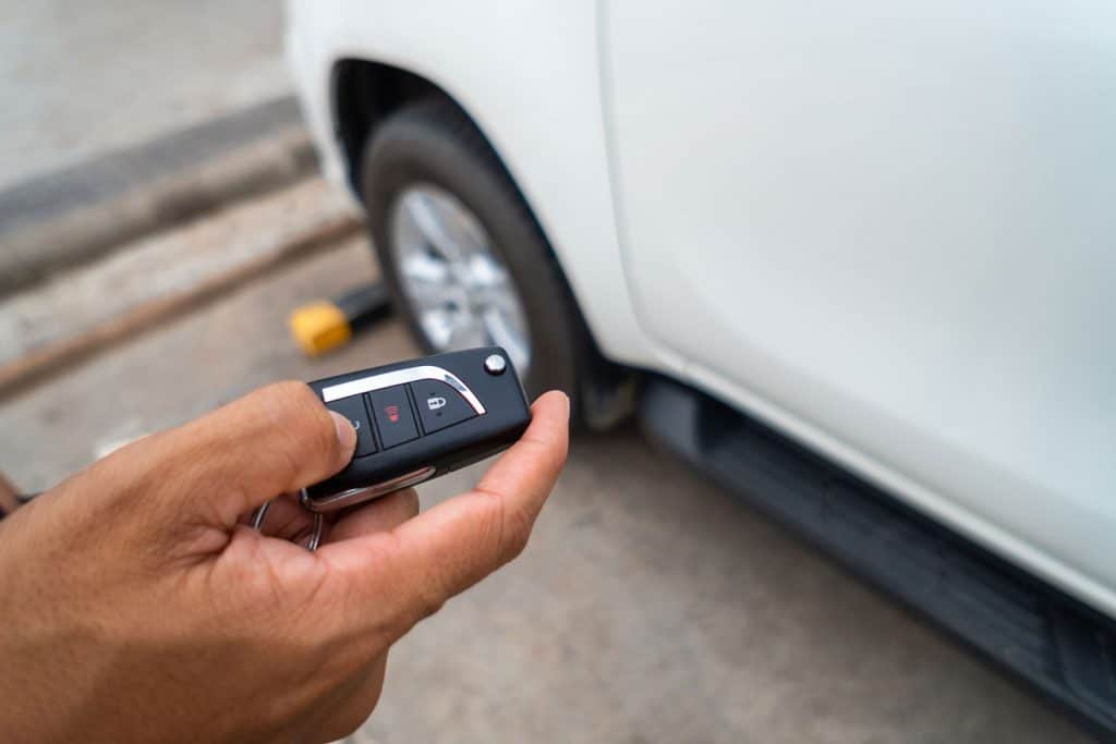 Hand pressing the button on the remote to lock or unlock the car with the remote control, How To Remote Start Hyundai Palisade