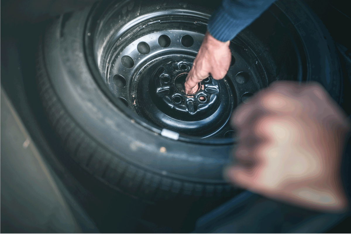 Man changing a tire, picking tire from the compartment