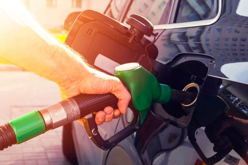 Man driver hand refilling and pumping gasoline oil the car with fuel at he refuel station, How To Open The Gas Tank On Hyundai Palisade