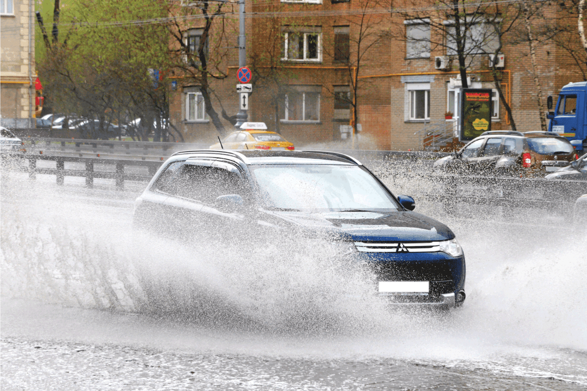 Motor car Mitsubishi Outlander in the city street during a heavy rain.