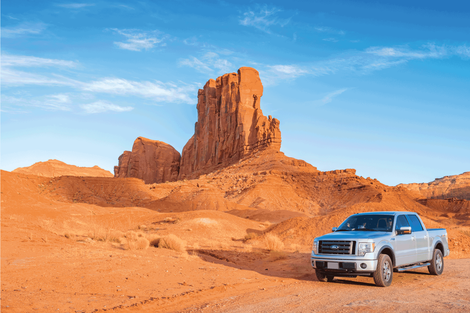 Pickup truck drives past scenic cliffs at the Monument Valley loop drive, Utah on a sunny day.