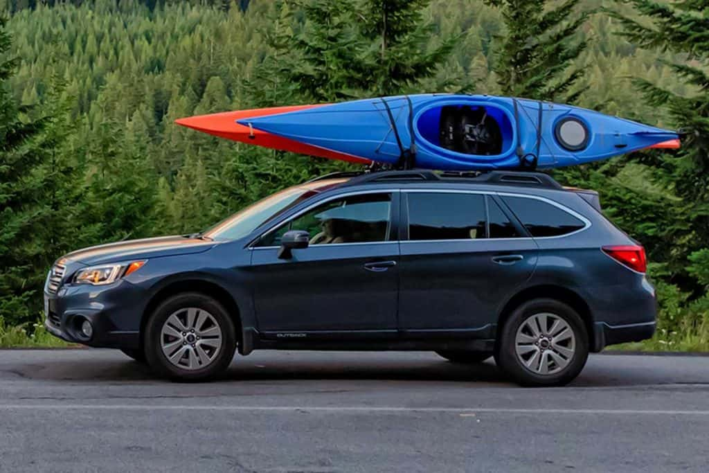 SUV with kayaks in front of mountain during sunset, What Are The Best Kayak Racks For Pickup Trucks? [6 Options Explored!]