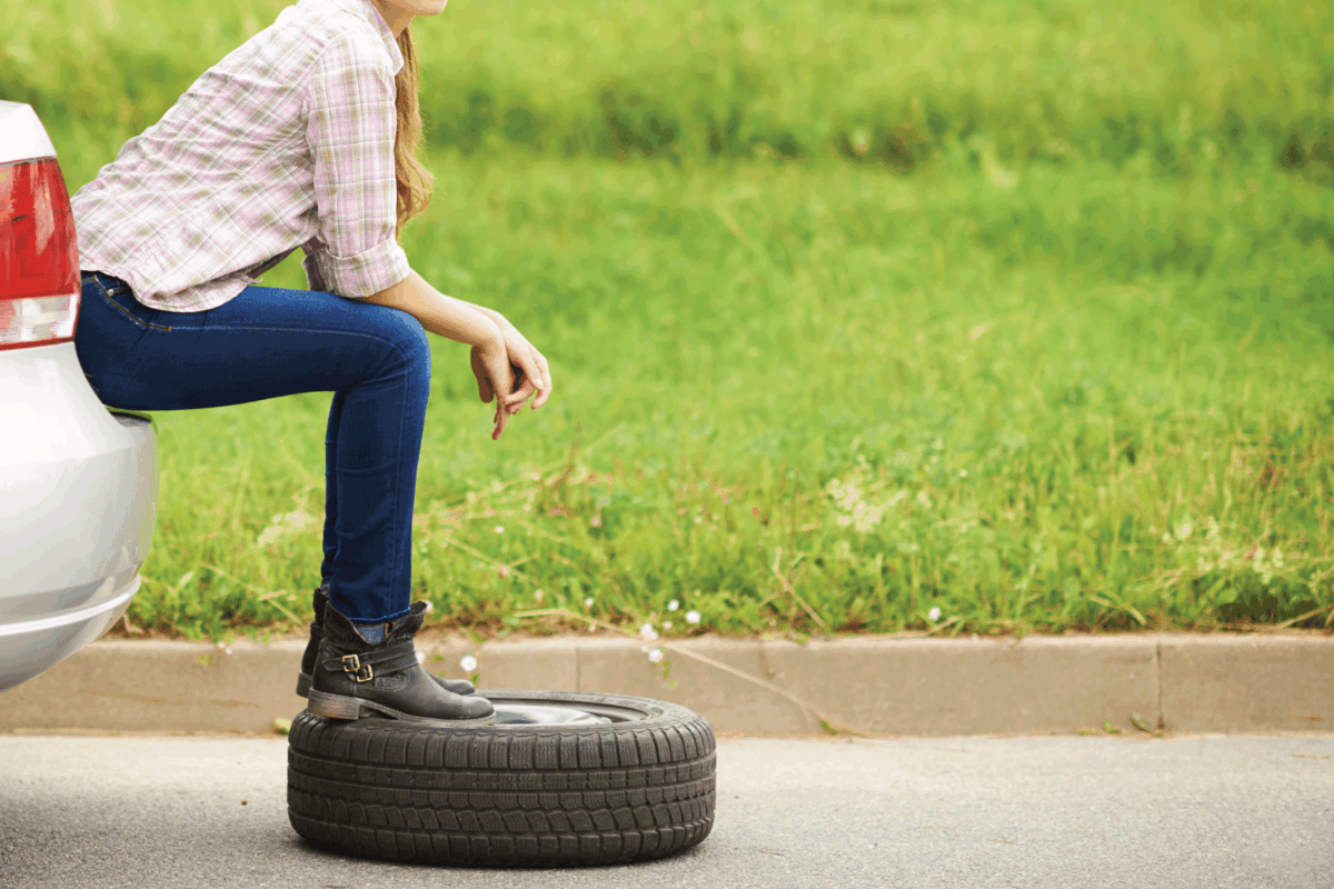 Shot of an attractive young woman sitting and waiting for roadside assistance after getting a flat tire
