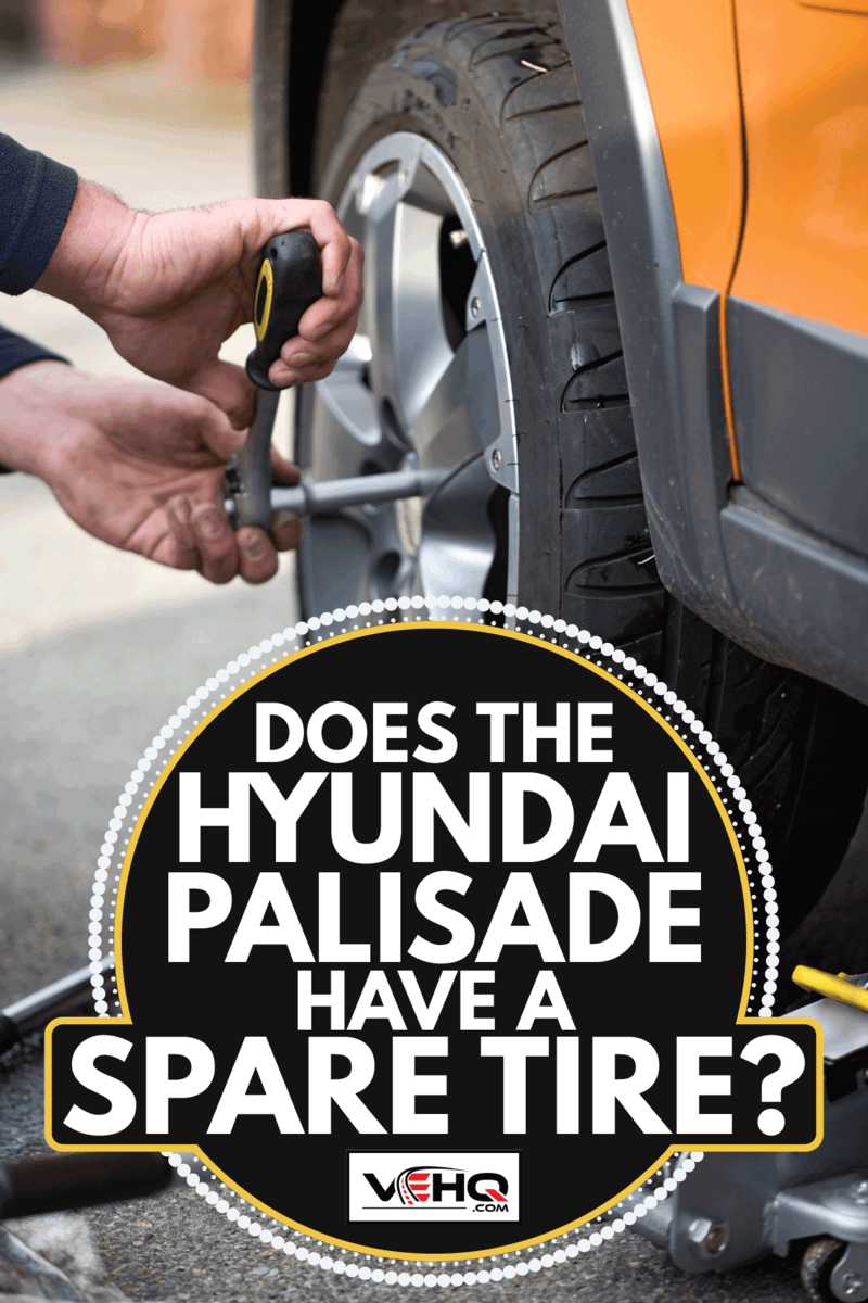 a man attaching a wheel to the car. Does The Hyundai Palisade Have A Spare Tire