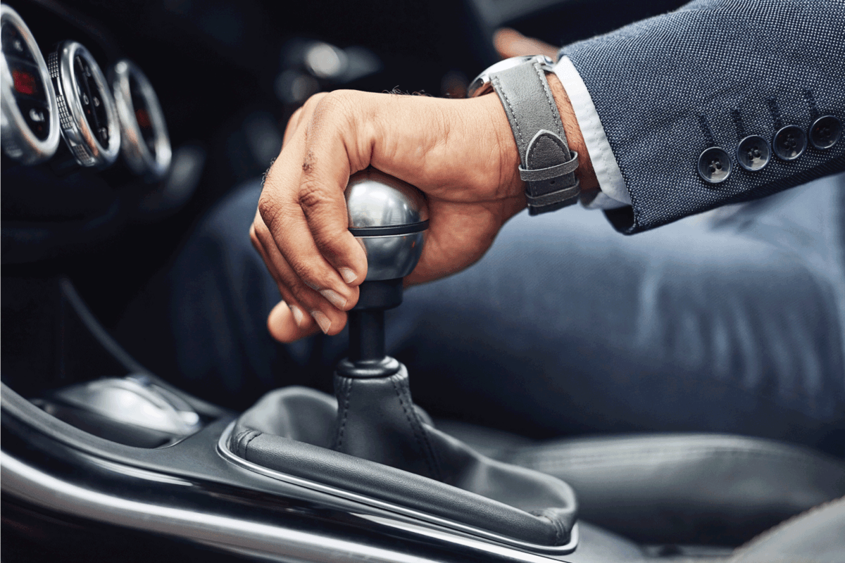 man's hand on his gearstick while driving