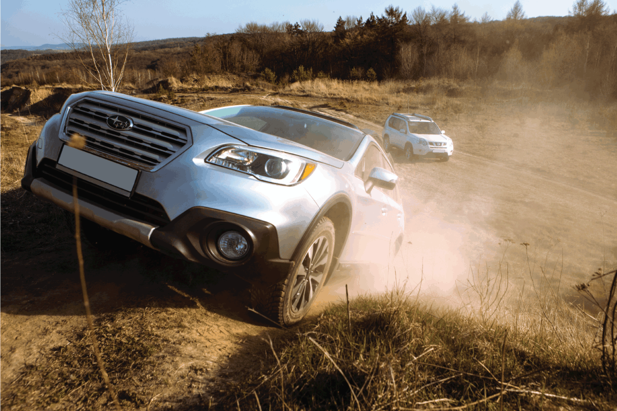 subaru outback suv car trying to get up by dusty hill. nissan x-trail on background. off road concept