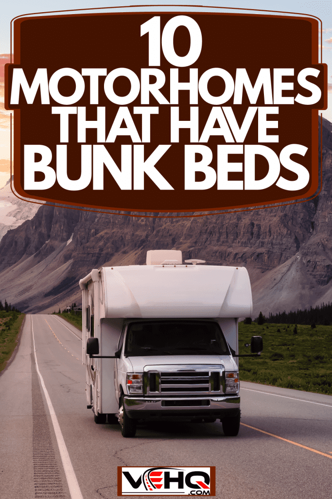 A Ford motorhome traveling on a long stretch of highway with a scenic view of the mountains on the background, 10 Motorhomes That Have Bunk Beds