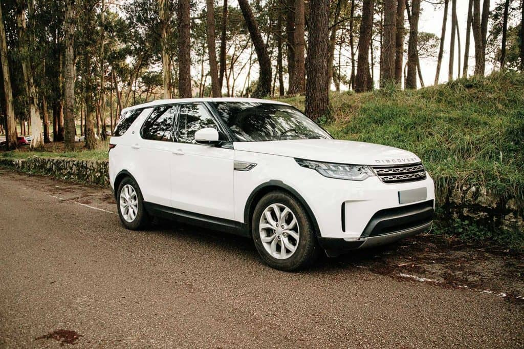 A Land Rover Discovery luxury SUV car stationary in a forest