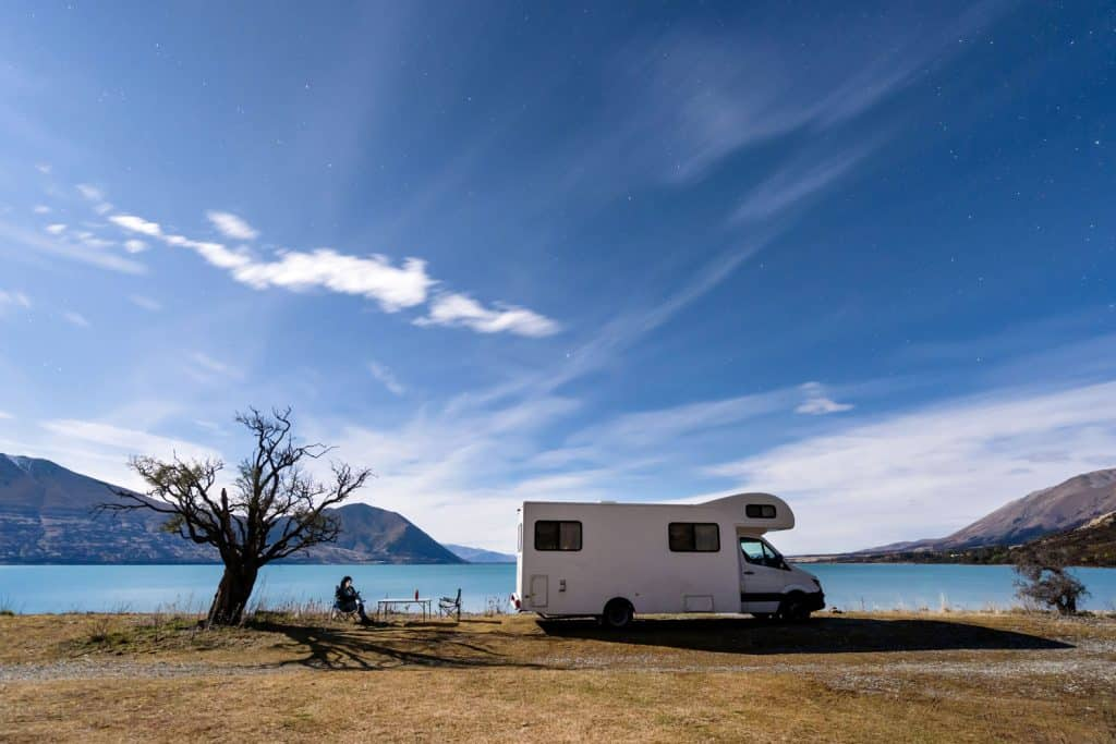 A gorgeous scenic view of a lake with crystal blue waters and a motorhome parked close to the waters