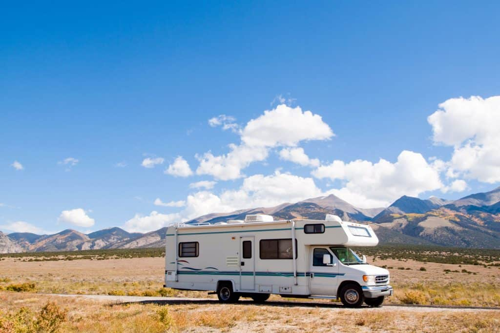 A long motorhome trekking on a long stretch of highway with a scenic view of mountains on the background
