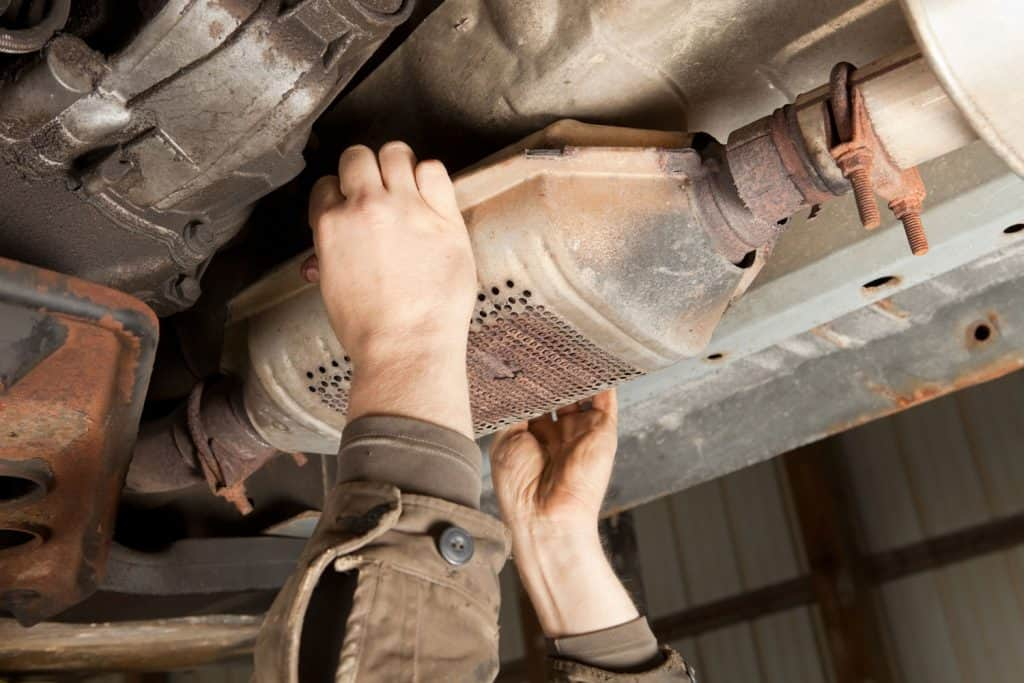 A man removing the catalytic converter of a car