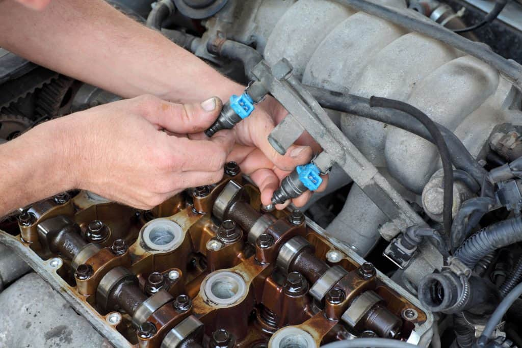 A mechanic checking the fuel injector of the engine
