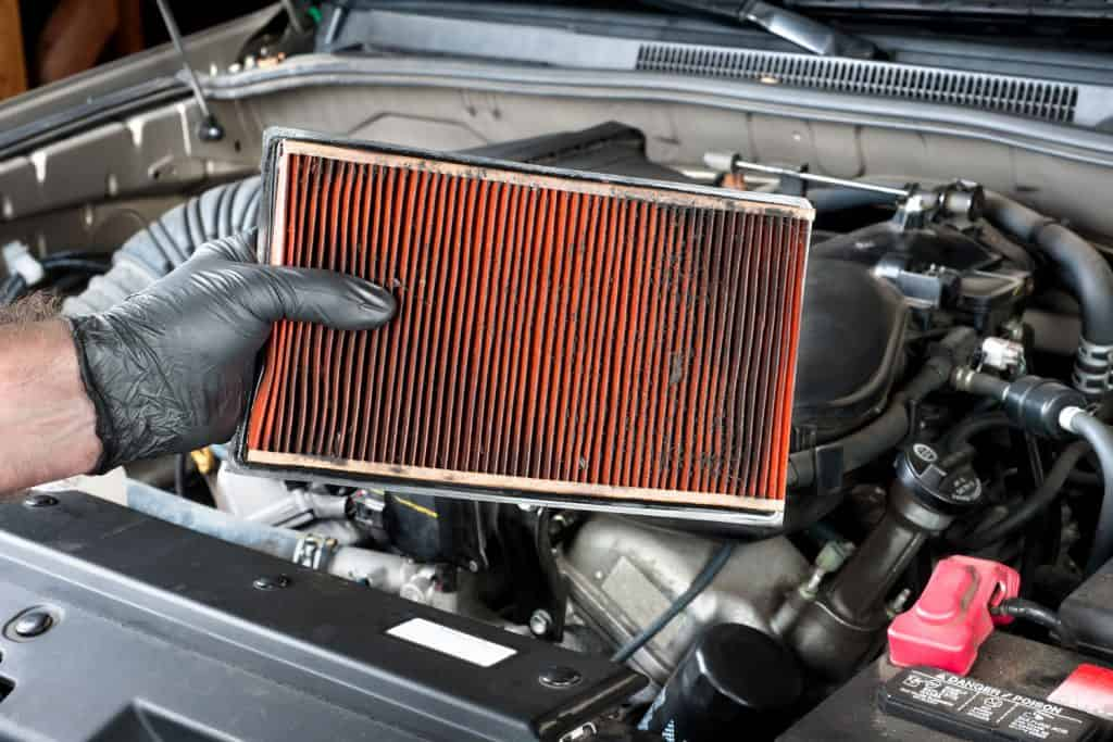 A mechanic holding a dirty air filter of a car