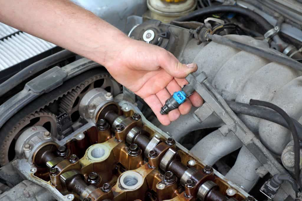A mechanic holding the fuel injector of a car