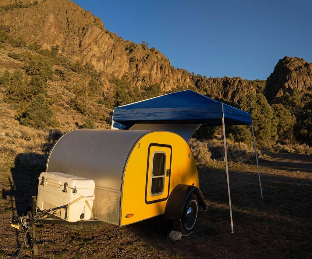 A teardrop style trailer camper with a shade structure and cooler