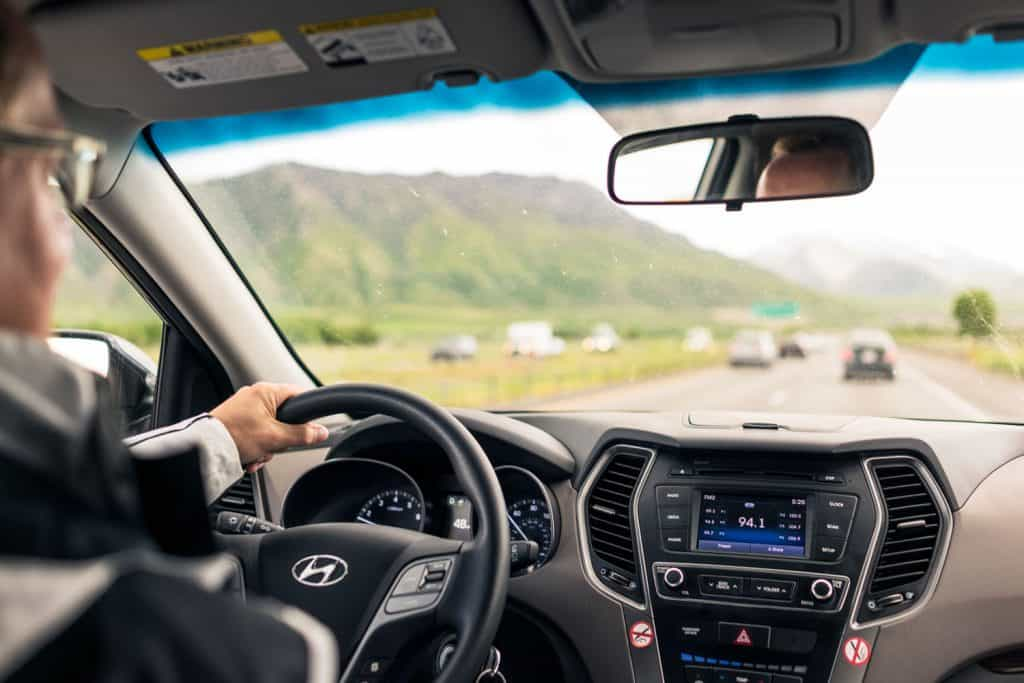 A view of a man driving a Hyundai SUV on a rural freeway, with light daytime traffic on the road ahead