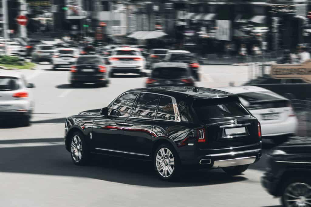 Black luxury British Rolls Royce Cullinan SUV in motion. Rolls Royce Cullinan in the city