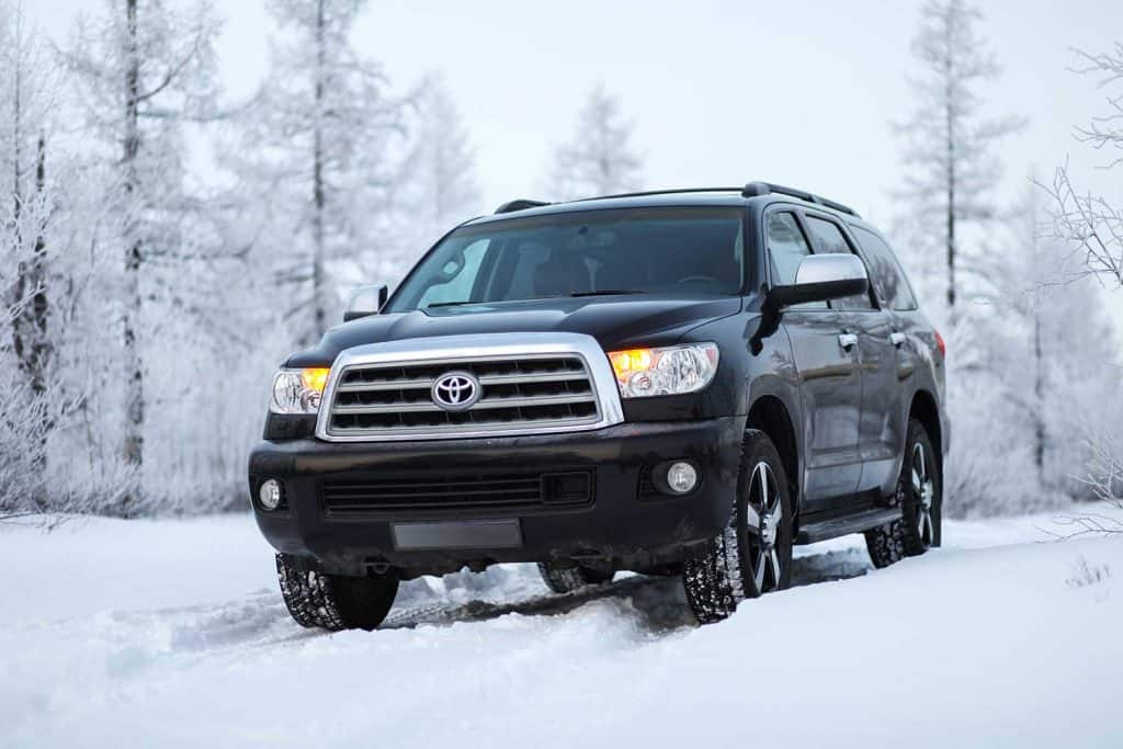 Black off-road vehicle Toyota Sequoia in the snow covered forest