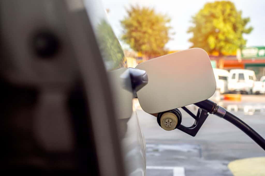 Car refueling on petrol station. Pumping gasoline fuel behind white fuel cap holder.