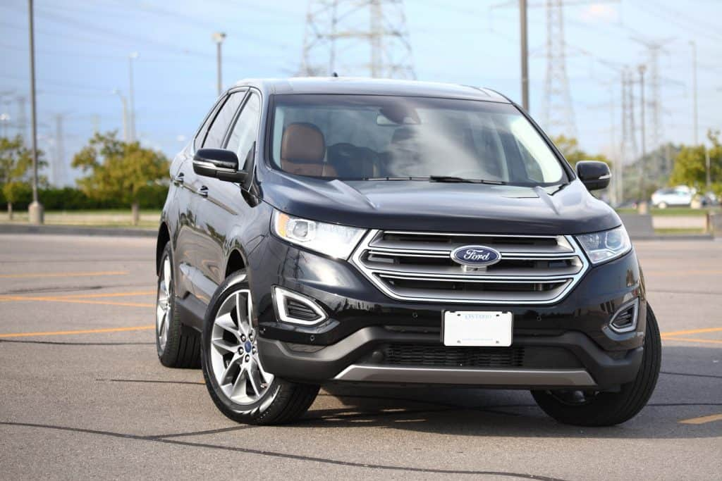 Close-up image of a brand new black Ford Edge 2016 Titanuim with cognac leather interior standing outdoors on a parking lot in summer