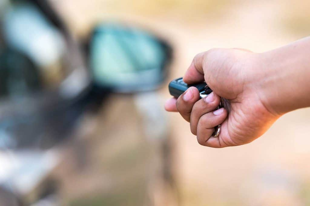 Close up of a man's hand pushing unlock button on car remote