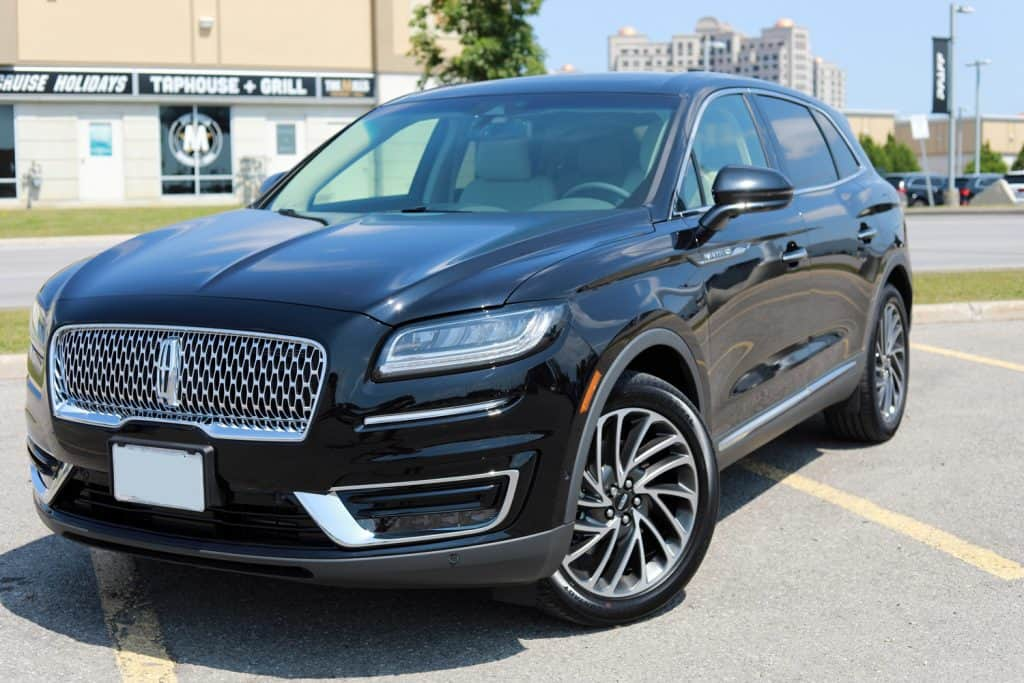 Front and side view of a brand new shiny Lincoln Nautilus 2019 Reserve model with premium 20 inch wheels in black color on an outdoor parking lot.