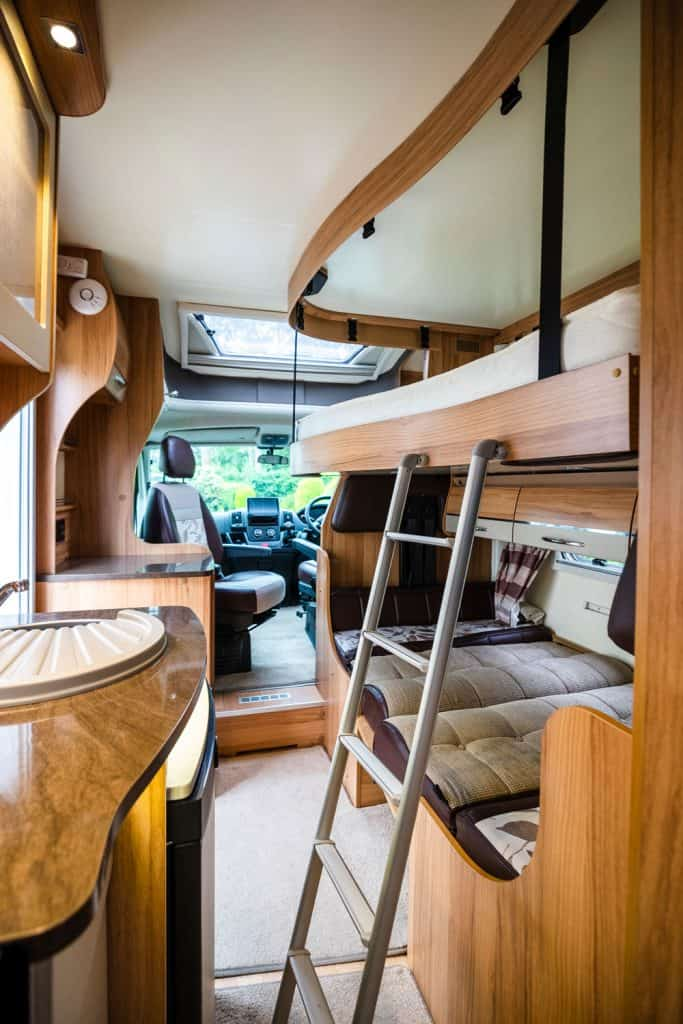 Interior of a motorhome with wooden framed top and bottom bunks beds