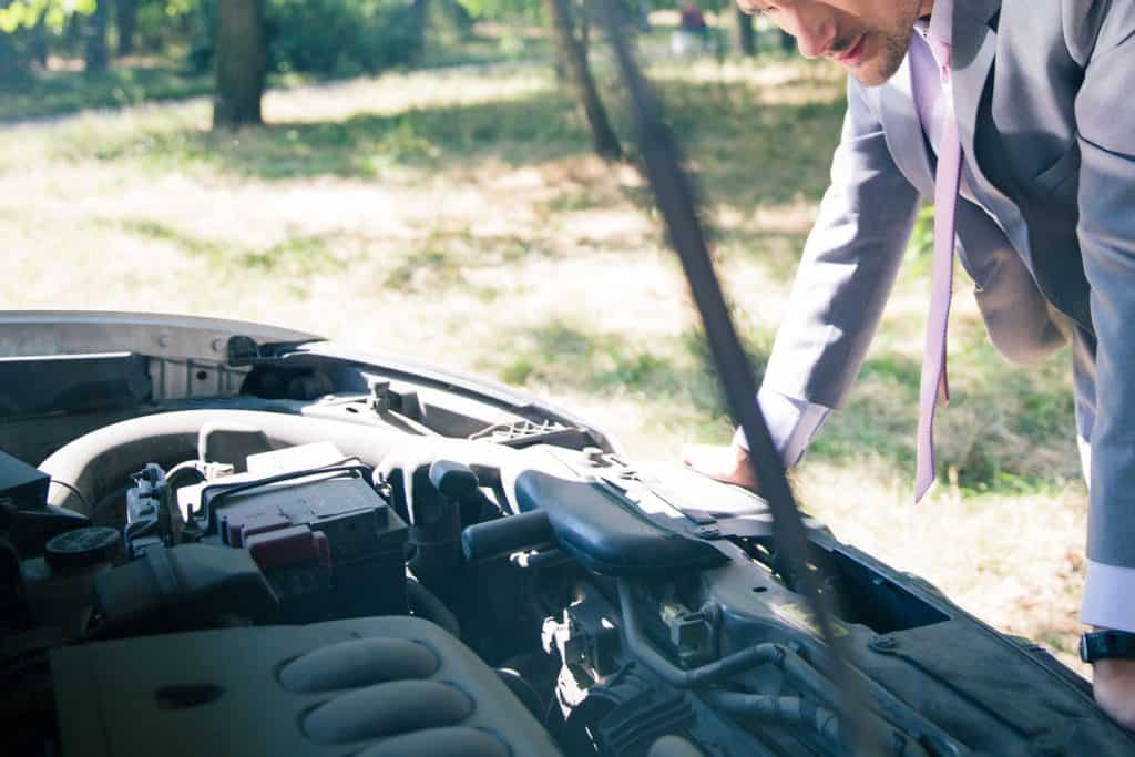 Man in suit looking under the hood of breakdown car, 10 Engine Misfire Symptoms Every Driver Should Know