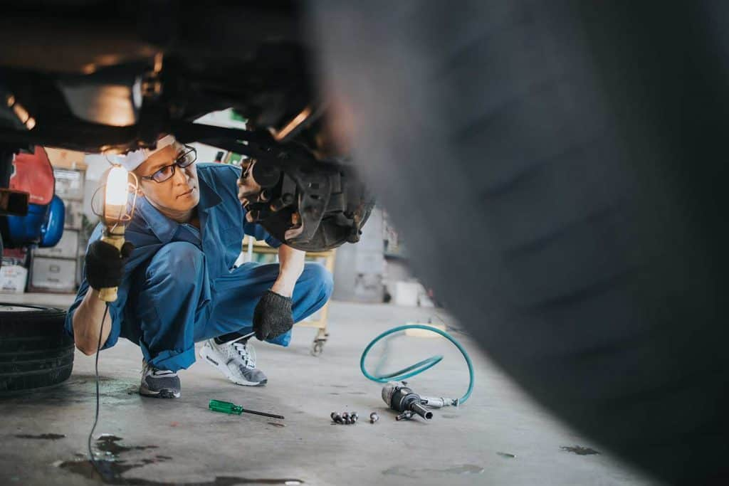 Mechanic with lamp working at car auto repair shop