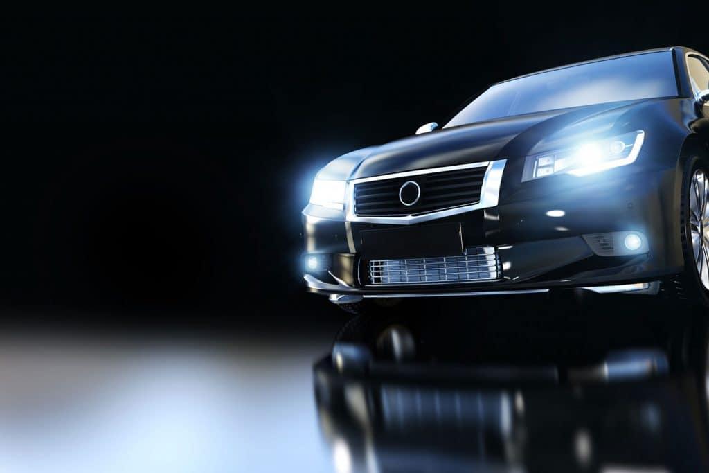 Modern black metallic sedan car in spotlight, Why Are My Car Headlights Not Bright Enough?