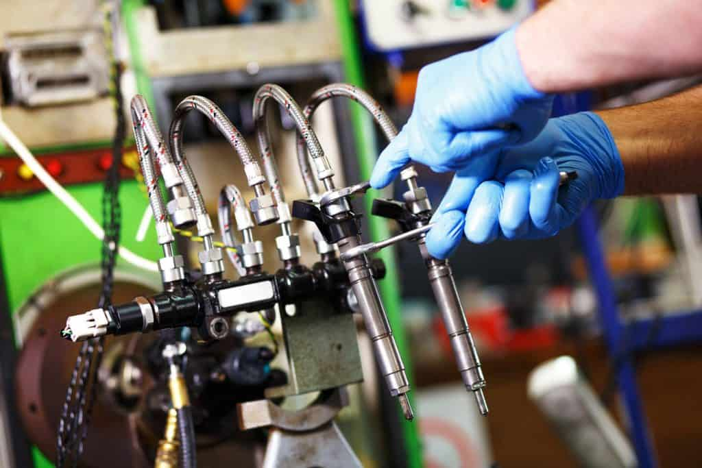 Professional mechanic testing diesel injector in his workshop, 5 Of The Best Fuel Injector Cleaners For Diesel Engines