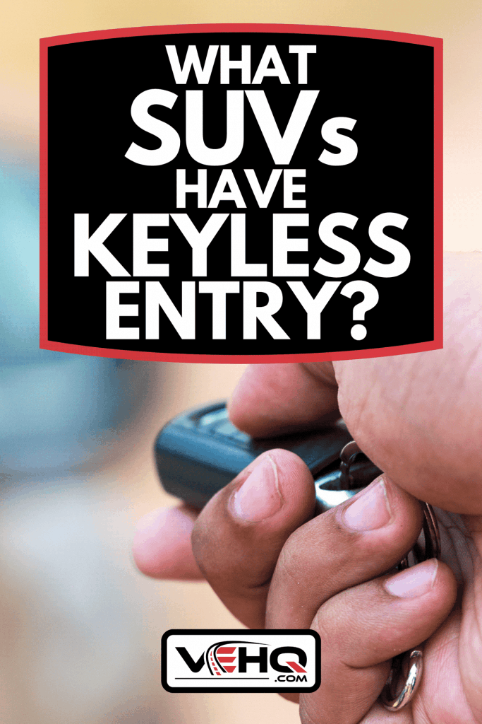 A man's hand pushing unlock button on car remote, What SUVs Have Keyless Entry?