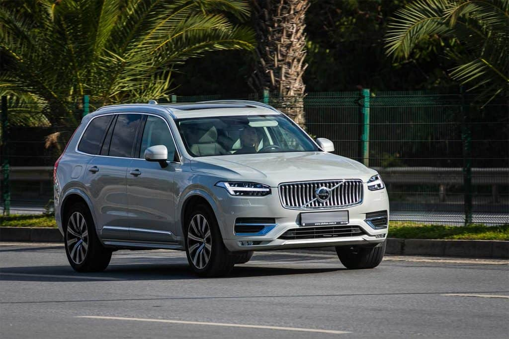 White Volvo XC90 is driving fast on the street on a warm summer day