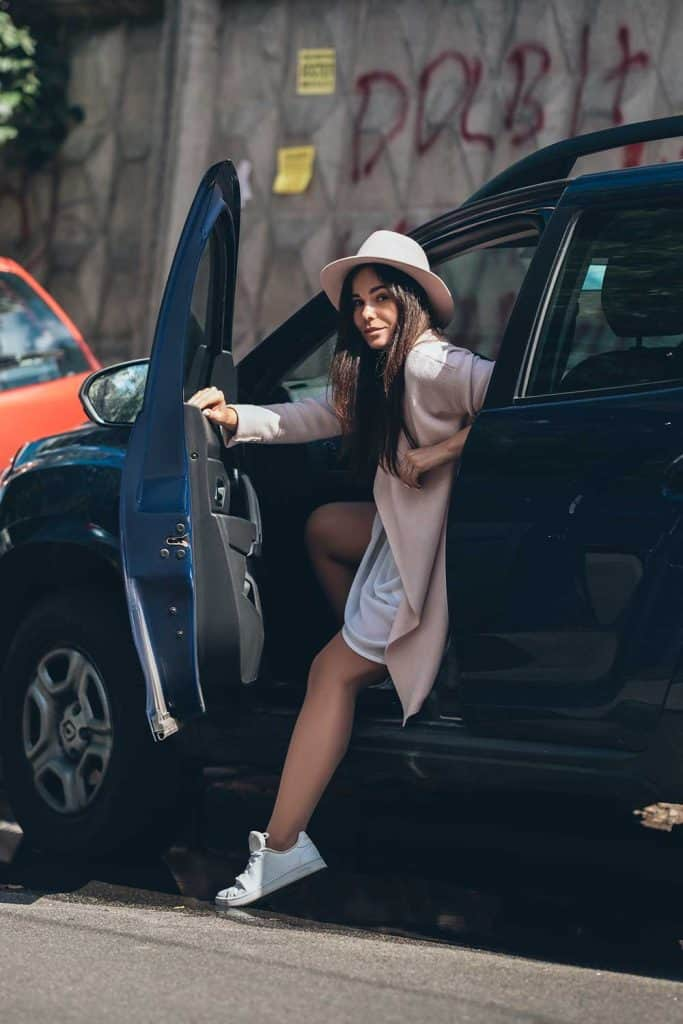 Young woman in casual outfit get out of SUV car on a summer day